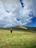 Woman hiking solitude on mountain meadow Royalty Free Stock Photography