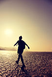 Woman hiking on sunrise beach Stock Photos