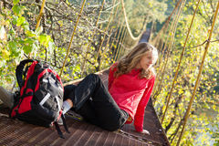 Woman hiking in suspension bridge and resting Royalty Free Stock Photography