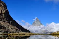 The woman hiking to Riffelsee lake in front of Matterhorn and cl Stock Photography