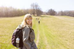 Woman is hiking and trekking outside on a hill. Tourism, vacation and fitness activity concept. Woman is hiking and trekking outside on a hill. Outdoor tourism stock image