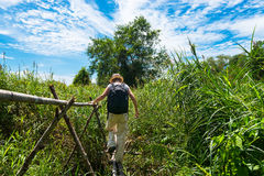 Woman hiking in tropical field Royalty Free Stock Image