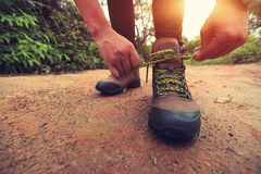 Woman hiking tying shoelace Stock Image