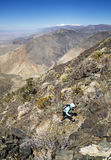 Woman Hiking Up Desert Mountain Stock Images