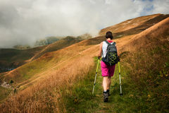 Woman hiking using hiking poles stock photos
