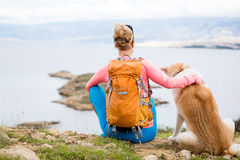 Woman hiking walking with dog on sea landscape Royalty Free Stock Image