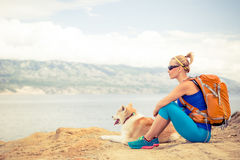 Woman hiking walking with dog on seaside trail. Woman hiking with akita inu dog on seaside trail. Recreation and healthy lifestyle outdoors in summer mountains stock images