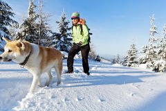 Woman hiking in winter with dog Stock Images