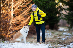 Woman hiking in winter forest with dog Stock Photo