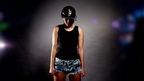 Woman hip hop dancing. Brunette woman woman in shorts and a cap hip hop dancing against a dark studio backbround stock video