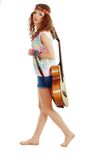 Woman in hippie outfit walking with guitar Royalty Free Stock Image