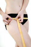 Woman hips measured. Young woman measuring the sides of the measuring tape Royalty Free Stock Image