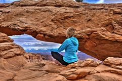 Woman hipster meditating at cliff by Mesa Arch. Canyonlands National Park.  La SAl Mountains. Moab. Utah. United States Stock Photos