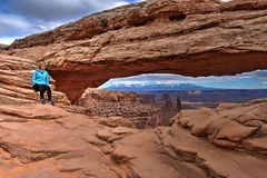 Woman hipster sitting on  cliff by Mesa Arch. Canyonlands National Park near Moab. Utah. United States Stock Photos