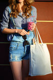 Woman Hipster with Smoothies in disposable cup, Linen Bag and sunglasses keep in their hands Royalty Free Stock Photos
