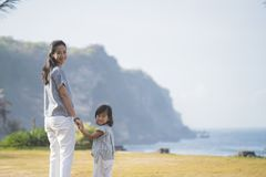 Woman and his daughter walking around park looking back at camer royalty free stock photo