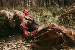 Woman in historical dress resting in autumn forest. Beautiful woman in historic dress resting in autumn forest Stock Photo