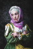 Woman historical era of the Middle Ages sitting. Medieval woman She is holding a book and a crucifix. Pray. In the old beautiful yellow-green dress. Historic royalty free stock images