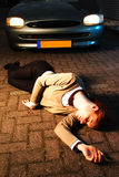 Woman Hit by a Car. A supposedly dead or injured woman laying on the ground after she has been hit by a car in an accident at night Royalty Free Stock Image