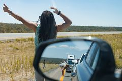 Woman hitch hikes Side mirror on car shows view of motorists stranded Massive traffic pile up on interstate 40 new mexico. People wait impatiently for road block stock photos