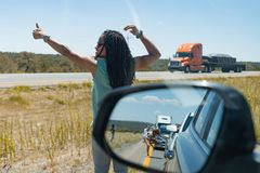 Woman hitch hikes Side mirror on car shows view of motorists stranded Massive traffic pile up on interstate 40 new mexico. People wait impatiently for road block stock photography