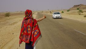 A woman hitch-hiking and catches a car stock image