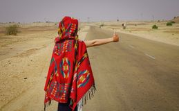 A woman hitch-hiking and catches a car royalty free stock images