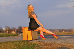 Woman hitch hiking on a country road Royalty Free Stock Photography