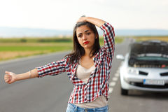 Woman hitch-hiking in front of her broken car Stock Images