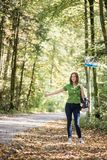 Woman hitchhiker standing on the side of the road in autumn fore Royalty Free Stock Image