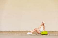 Woman hitchhiker with suitcase sitting on road Stock Photos