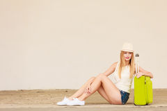 Woman hitchhiker with suitcase sitting on road Royalty Free Stock Photos