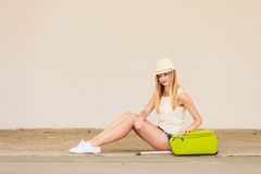 Woman hitchhiker with suitcase sitting on road Royalty Free Stock Image