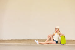 Woman hitchhiker with suitcase sitting on road. Travel, adventure, teenage journey concept. Woman wearing denim shorts, white top and sun hat suitcase holding Royalty Free Stock Images