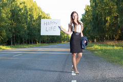 Woman hitchhikes for happy life Royalty Free Stock Photos