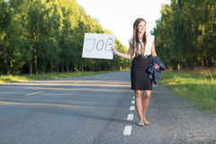 Woman hitchhikes for job. On road Royalty Free Stock Photography