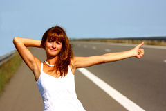 Woman hitchhiking. On a highway holding her hair Royalty Free Stock Photography