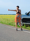Woman hitchhiking after a breakdown. Elegant woman in a sundress and stilettoes hitchhiking at the side of a country road after a breakdown Stock Photos