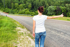 Woman hitchhiking Royalty Free Stock Image