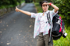 Woman hitchhiking on countryside road. In forest Stock Photos