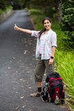 Woman hitchhiking on countryside road. In forest Royalty Free Stock Photos