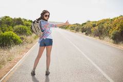 Woman hitchhiking on countryside road Royalty Free Stock Image