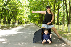 Woman hitchhiking with her son. Casual pretty barefoot women hitchhiking with her son who is sitting inside their suitcase on a rural tree-lined avenue Royalty Free Stock Photos