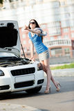 Woman hitchhiking near the broken white car Royalty Free Stock Photography