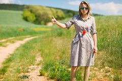 A woman in hitchhiking off road during sunny day royalty free stock photos