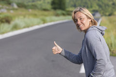Woman hitchhiking Royalty Free Stock Images