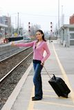 Woman hitchhiking at railroad station Royalty Free Stock Photo