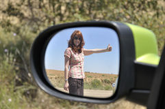 Woman hitchhiking reflected in the rearview mirror Stock Images