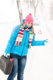 Woman hitchhiking on road snow gas can. Car breakdown problem royalty free stock photos