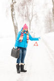 Woman hitchhiking on road snow gas can. Car breakdown problem stock images